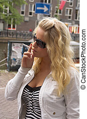 blonde with cigarette - Sexy blond girl in sunglasses...