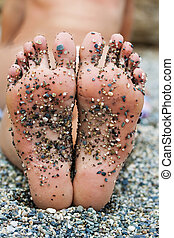 Foots with sand on it of woman laying on beach