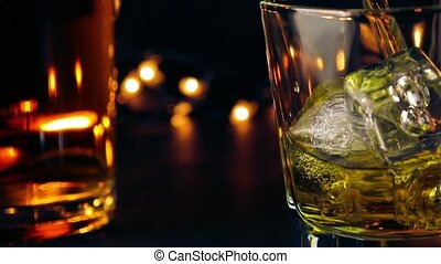 barman pouring whiskey on bar table in front of bottles on...