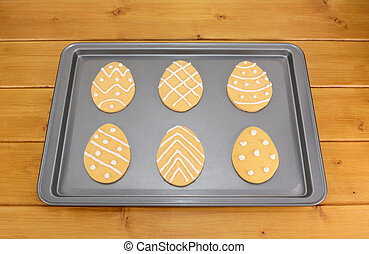 Frosted Easter egg cookies on a baking tray