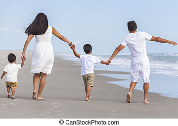 Mother, Father & Two Boy Children Family Walking on Beach -...
