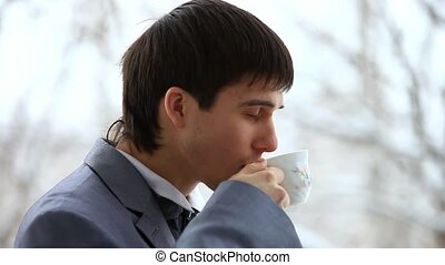 Handsome businessman stands in office by window with coffee cup, speaks to mobile phone, concentrating and smiling. HD. 1920x1080