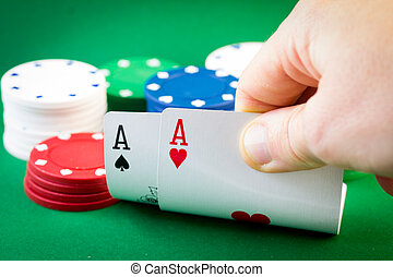Poker - Two Aces and chips - Player looking down at a pocket...