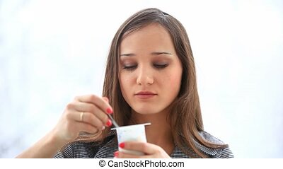 Cute, attractive woman eating yoghurt on white background HD...