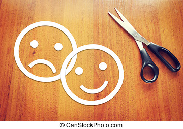 Sad and happy emoticons made of paper on the desk. Concept...