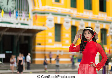 Stylish young Vietnamese woman in red standing raising her...