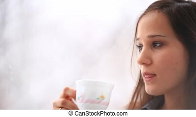 Woman drinking a cup of tea speaking mobile smart phone. HD....