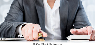 Successful accountant counting gold coins