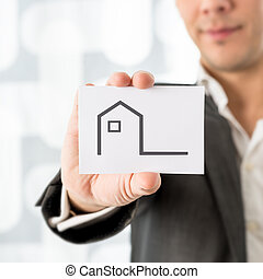 Businessman holding up a house icon on a card in a...