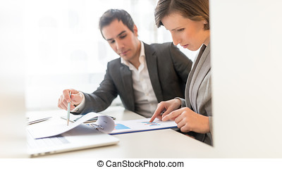 Business People Reviewing Business Reports Seriously While...