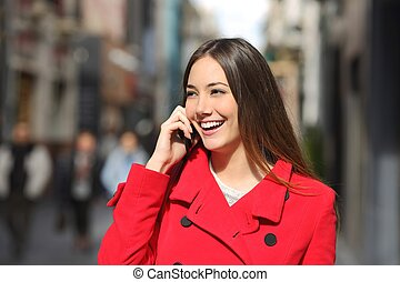 Cheerful woman talking on the phone in the street wearing a...