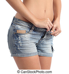 Fitness woman buttoning her shorts diet concept - Closeup of...