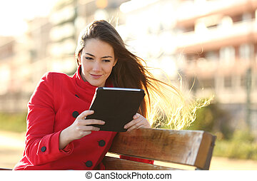 Woman reading an ebook or tablet in an urban park with...