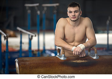 Portrait of a handsome gymnast with naked torso gymnastic...