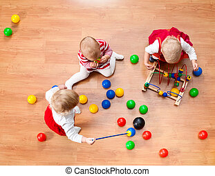 Playing toddlers - Top view of three little girls playing on...