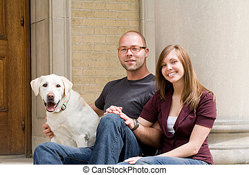 Happy Young Couple Smiling With Their Dog