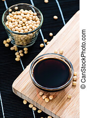 Portion of Soy Sauce - Small bowl with Soy Sauce on Bamboo...