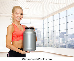 smiling spory woman holding protein jar - sport, fitness,...