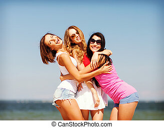 group of girls chilling on the beach - summer holidays and...