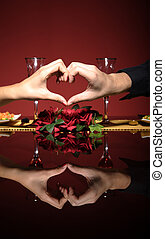 Close up of young couple at restaurant table with hands...