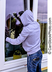 burglar at a window - a burglar trying to break in an open...
