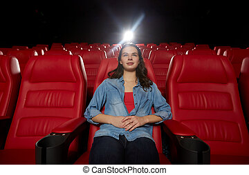 young woman watching movie in theater