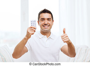 happy man with pack of pills showing thumbs up - people,...