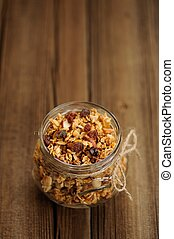 Granola in jar with packing-twine on wooden background with...