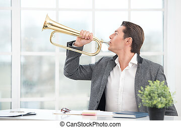 Businessman playing the trumpet in office