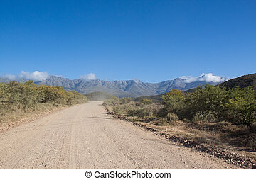 Dirt road leading over high mountain pass in daytime