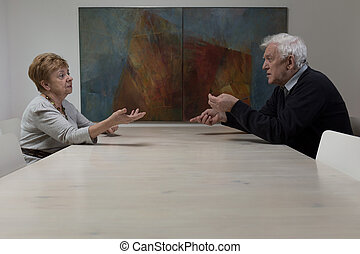 Sitting at the table and arguing - Older marriage sitting at...