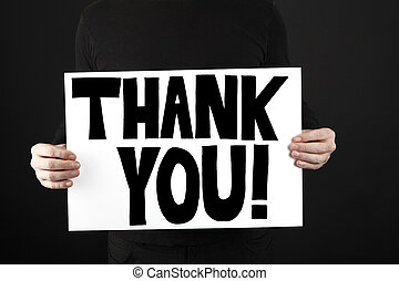Man holding poster with thank you in front of a black...