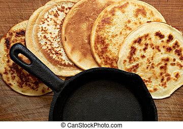 4 pancake - four round pancakes and cast iron skillet on a...