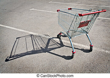 shopping cart in the parking lot of a supermarket