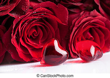 red roses flowers and two hearts, focus on the foreground
