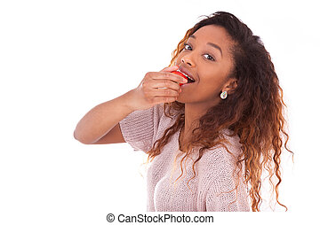 African American young woman eating a strawberry - Black people