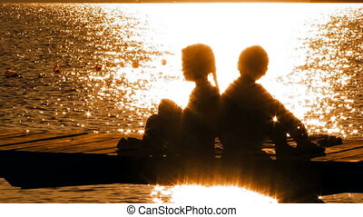 Little Boy and Girl Sitting On Bridge At Sunset