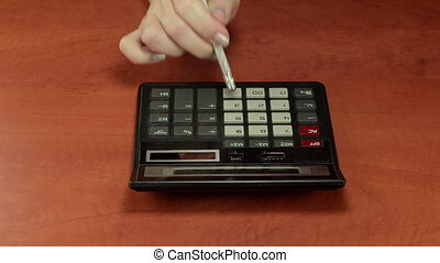 Calculator and pencil eraser - Woman right hand is pushing...