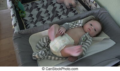 Baby on Changing Table on Pack - Newborn baby in diapers on...