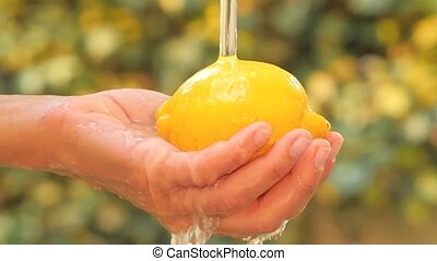 lemon close up - lemon in hand under flowing water slow...