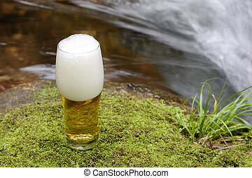 Glass beer on the moss at brook side