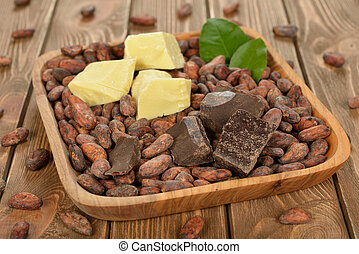Cocoa beans, cocoa butter and cocoa mass on brown background