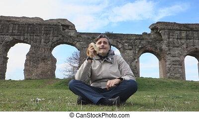 Man eating banana under Roman acqueducts ruins