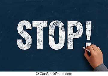 Stop - Businessman is writing stop text on blue chalkboard.