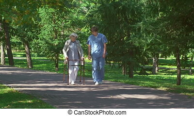 Professional Support - Elderly lady with walker and young...