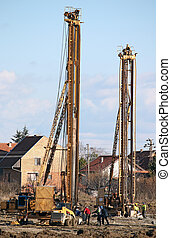workers and two hydraulic drilling machines on construction...