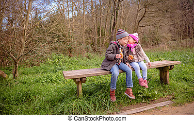 Little girl talking to the ear of boy sitting on bench -...