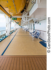 Chairs on Deck of Cruise Ship Under Lifeboats - Deck of a...