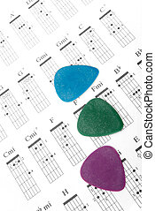 Colorful guitar picks on a chords chart