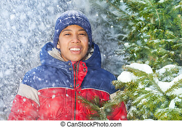 Portrait of smiling boy with falling snow flakes - Portrait...
